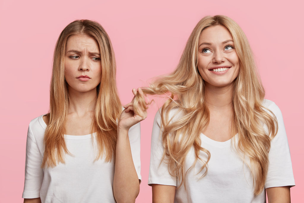 Two girls with blonde hair. One girl has moe limp oily hair and is holding the other girls hair, which looks cleaner, with an annoyed look on her face.