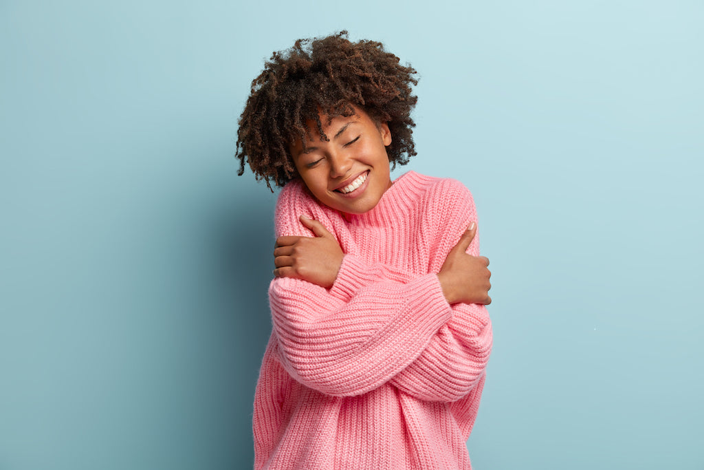Woman in pink sweater hugging self