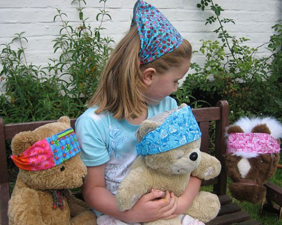 Girl and teddies all wearing hairbands together