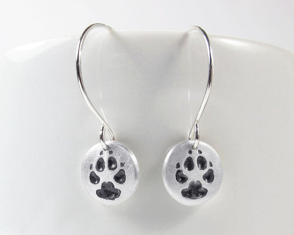 Tiny paw print earrings in silver