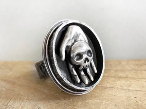 Hand Holding Skull Ring in Sterling Silver