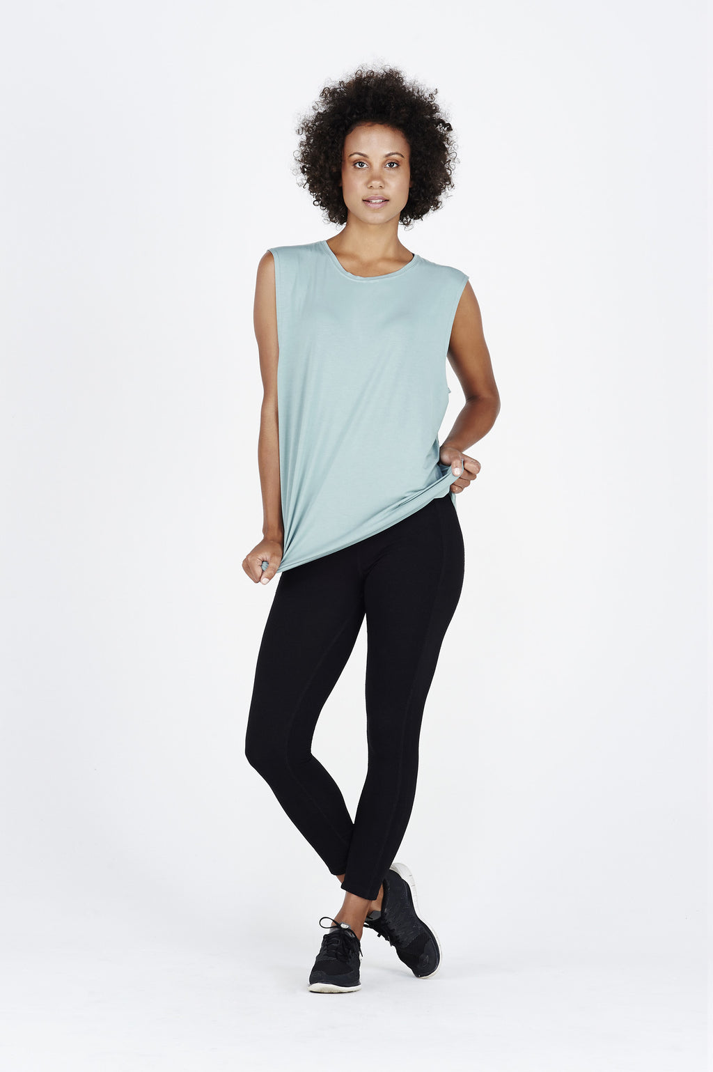 Woman afro wearing BAM.U bamboo muscle tank in teal over black BAM.U bamboo low impact leggings