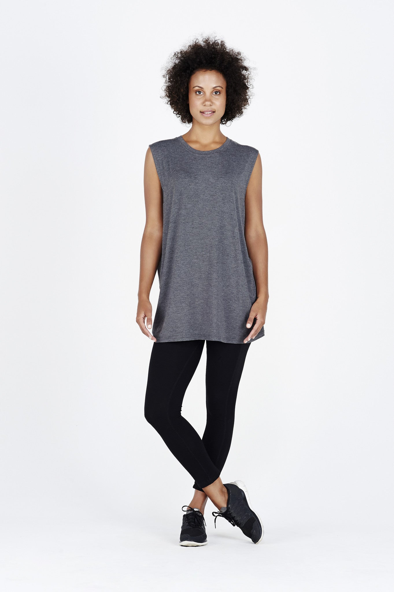 Woman with afro wearing charcoal BAM.U bamboo muscle tank over black BAM.U low impact bamboo leggings