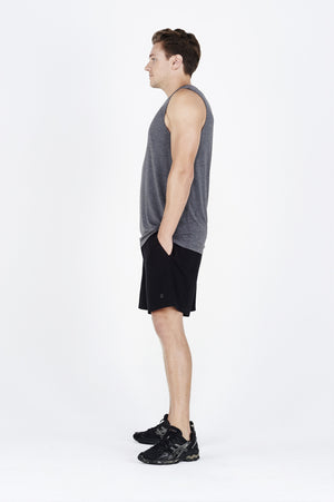 Guy side on wearing charcoal BAM.U training muscle tank over black BAM.U training basketball bamboo shorts