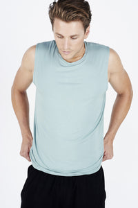 Guy looking down wearing teal BAM.U training muscle tank over black BAM.U training basketball bamboo shorts