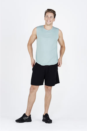 Guy smiling wearing teal BAM.U training muscle tank over black BAM.U training basketball bamboo shorts