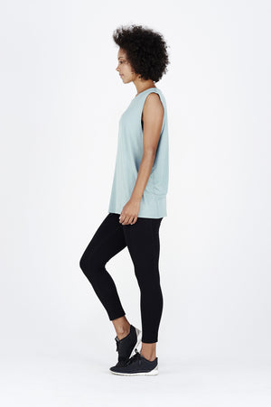 Woman with afro wearing teal BAM.U bamboo muscle tank over black BAM.U low impact bamboo leggings