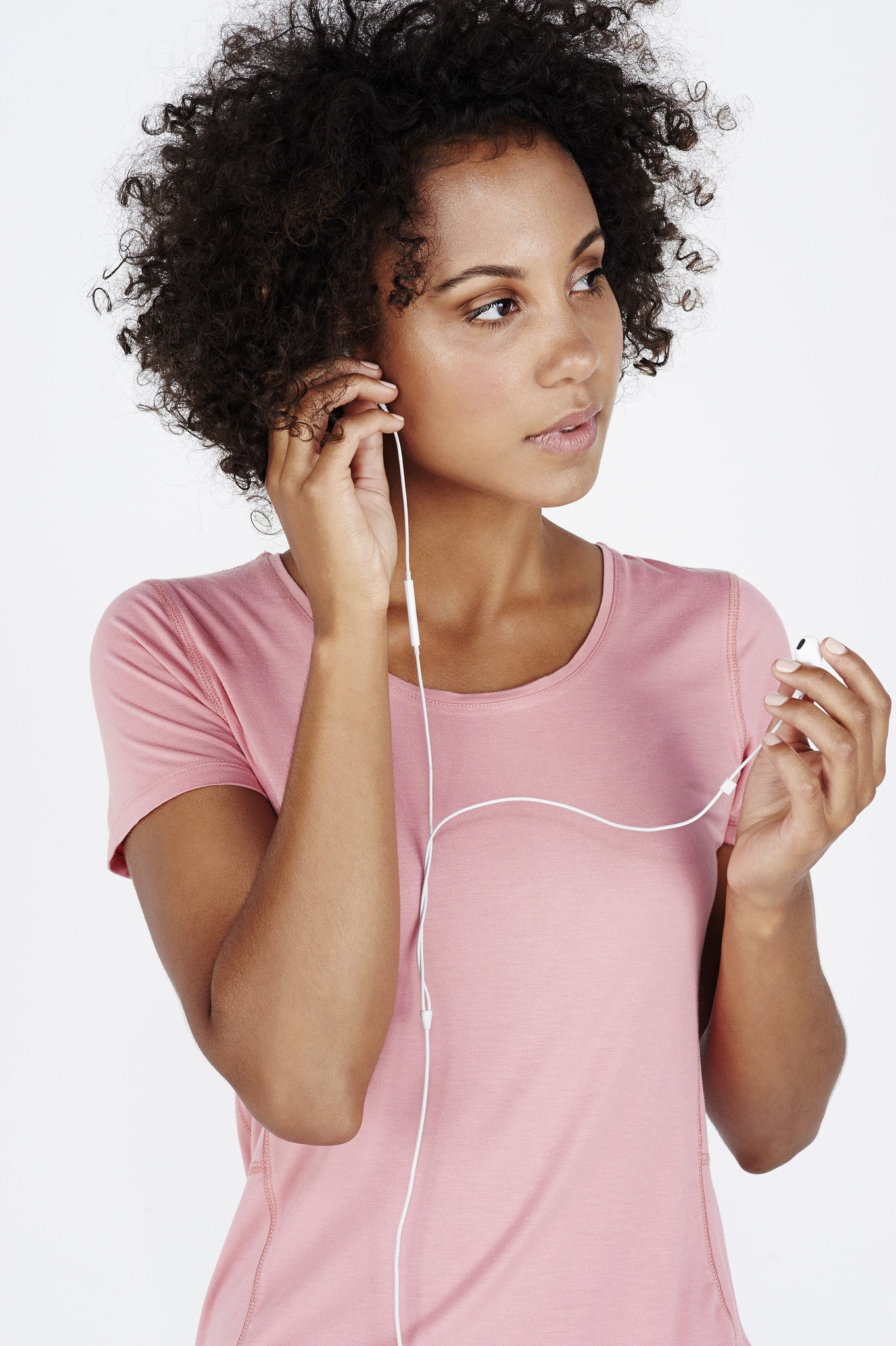 Woman with afro wearing coral BAM.U bamboo run tee putting in ipone ipod earphones