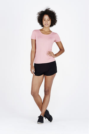 Woman with afro wearing coral BAM.U bamboo run tee over black BAM.U gym run shorts in bamboo