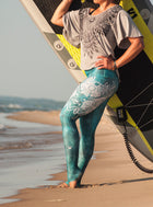 Teal High waisted yoga leggings with white deer design from Inner Fire.  Uniquely Yoga Majestic workout pants on beach with stand up paddle board