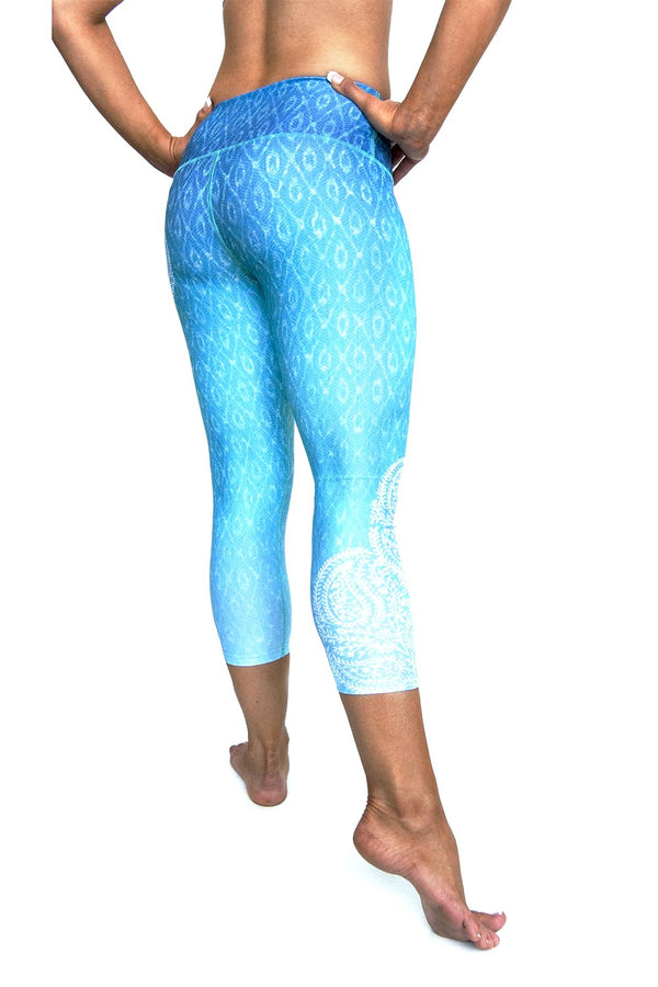 Reflection Blue green white ombre high waisted compression capri with asymmetrical white  pattern on side over water reflection print from Inner Fire. Premium fabrics made from recycled water bottles. Back view