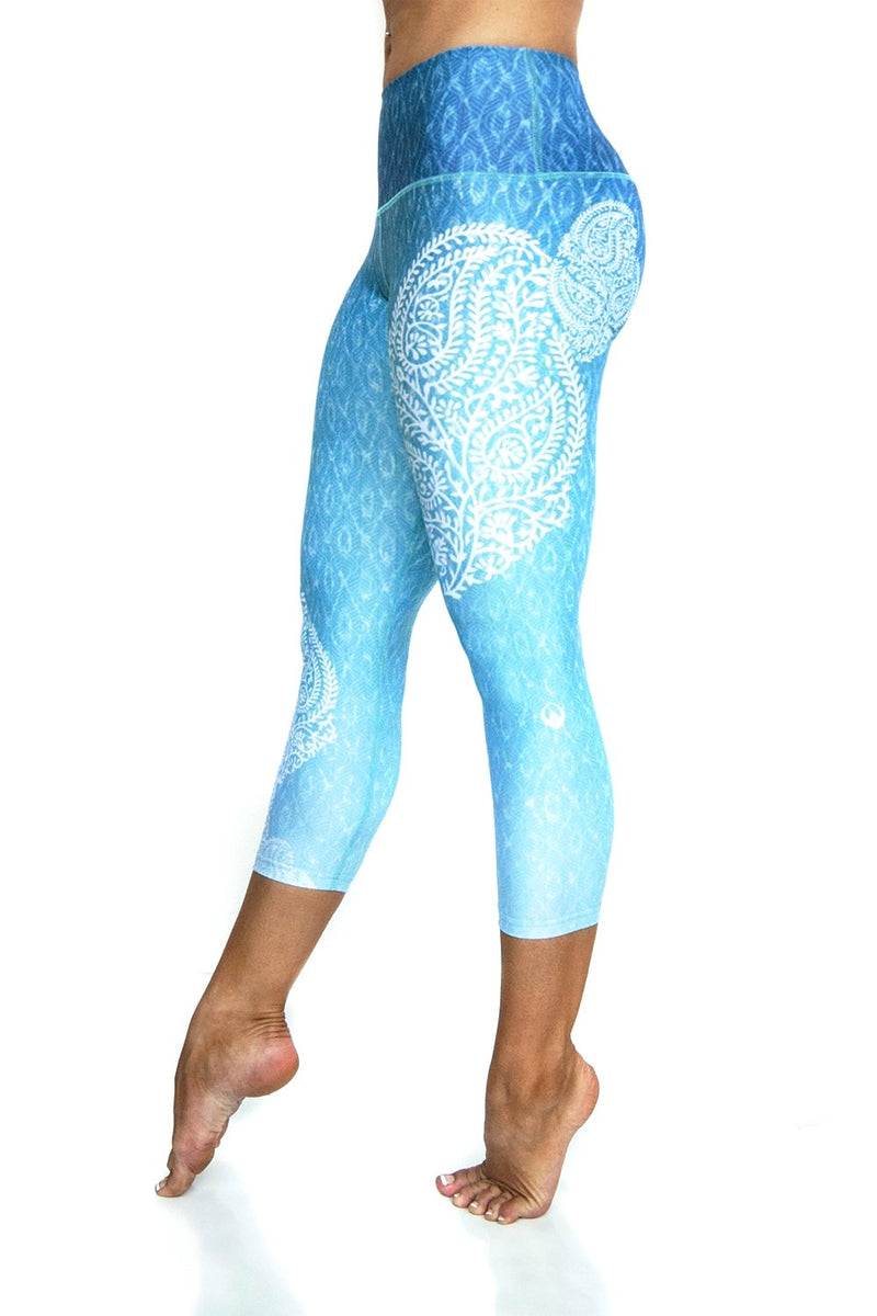 Reflection Blue green white ombre high waisted compression capri with asymmetrical white  pattern on side over water reflection print from Inner Fire. Premium fabrics made from recycled water bottles. Side view