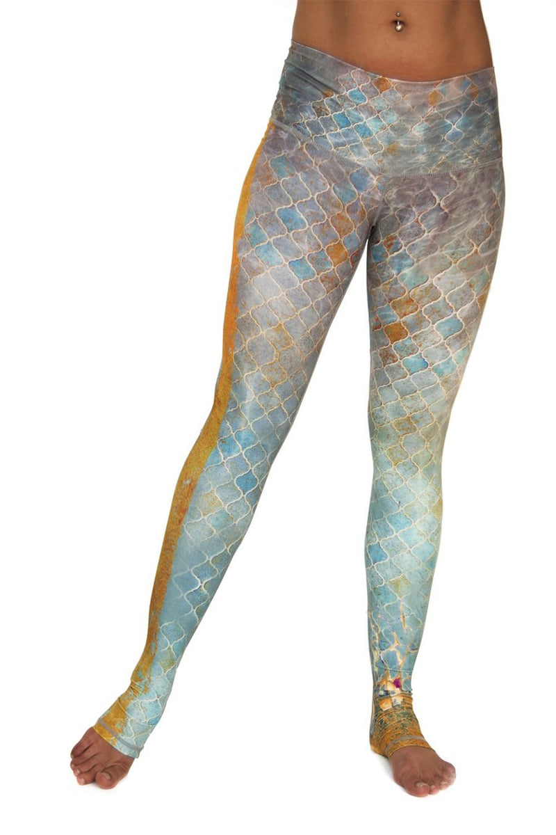 Sahara leggings high waist extra long soft compression fabric in desert tile multi color design. Blue tan and pink asymmetrical design with yellow stripe down single leg from Niyama Sol. Available from Uniquely Yoga. Front View