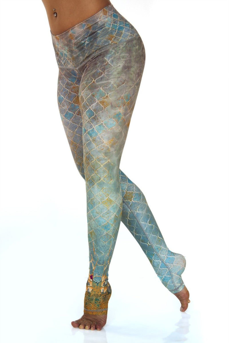 Sahara leggings high waist extra long soft compression fabric in desert tile multi color design. Blue tan and pink asymmetrical design with yellow stripe down single leg from Niyama Sol. Available from Uniquely Yoga. Left View