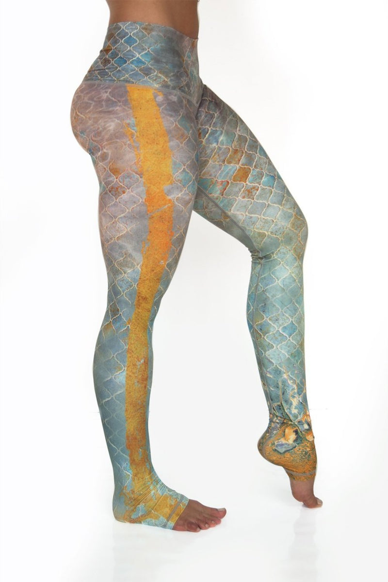 Sahara leggings high waist extra long soft compression fabric in desert tile multi color design. Blue tan and pink asymmetrical design with yellow stripe down single leg from Niyama Sol. Available from Uniquely Yoga. Right Side
