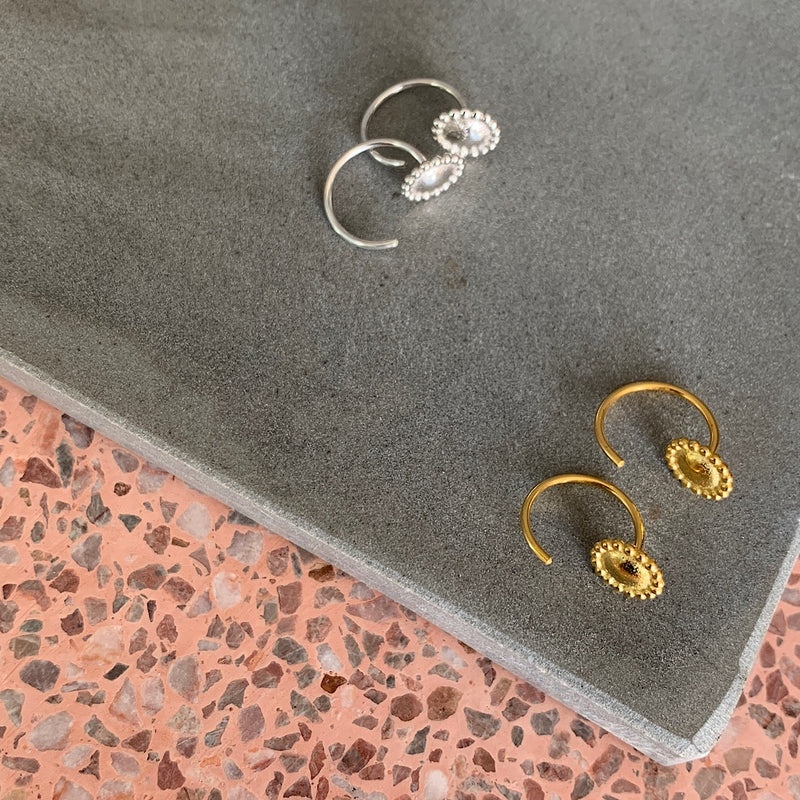 flatlay of the kath curve hoops in sterling silver and gold