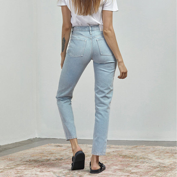 model wears the lucy jean classic slim fitting light blue high rise denim by outland denim
