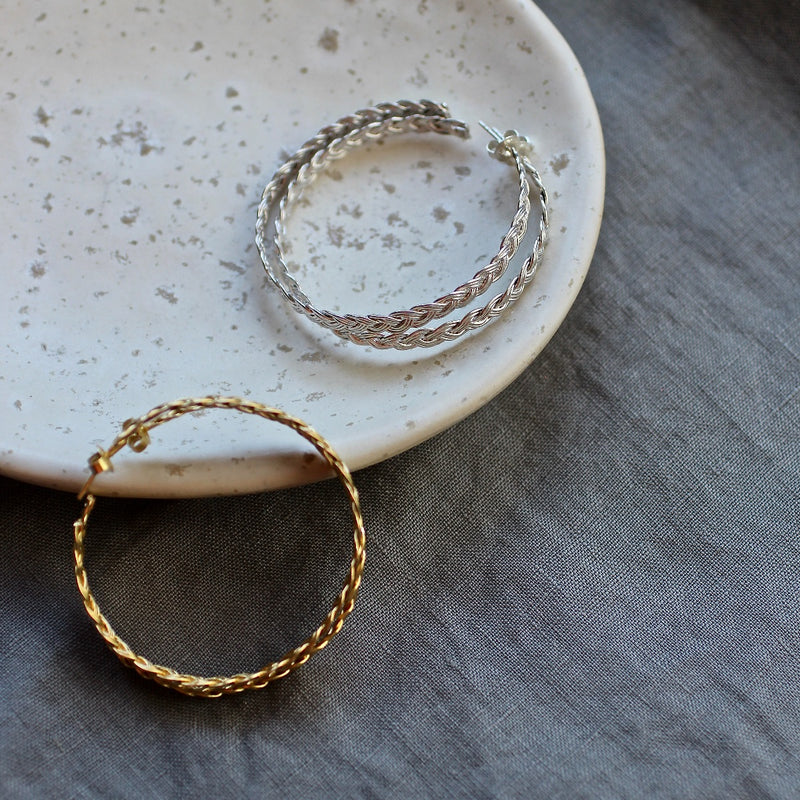 flatlay of the rebecca woven braided large big hoops hoop earrings in sterling silver gold plate or sterling silver