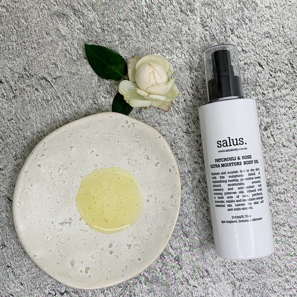 Salus Rose body oil pump and oil on a plate