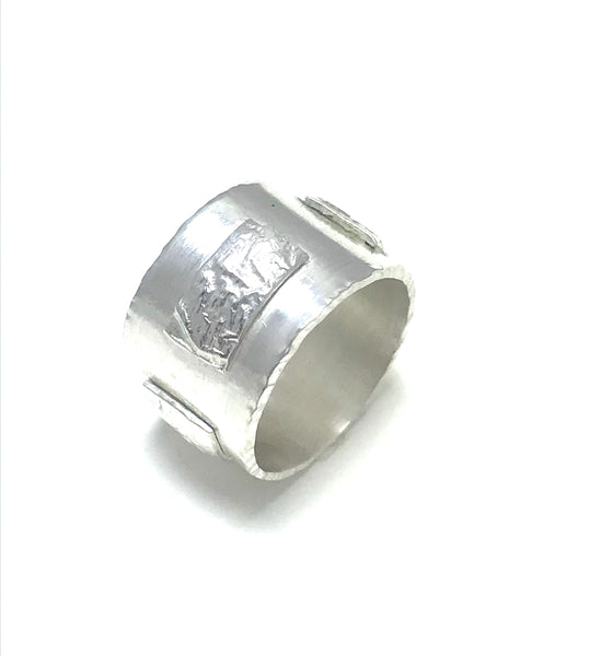 Thick Sterling silver band with rectangular textured recticulated silver accents.