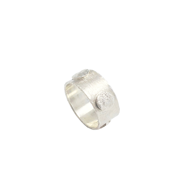 Circular band of silver with raised textured circles with tactile interest.