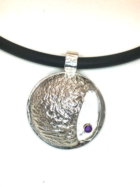 "1 1/4"" round diameter of reticulated silver with the texture of a mountain range.  Includes a bright purple amethyst in a gold tube setting.   The overall shape is a circle with a small open side-pocket."