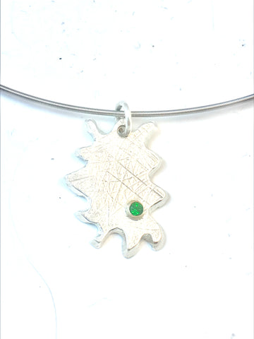 "A close up photo of a sterling silver pendant that looks like a puzzle piece. For accent, a green chrome diopside measuring 3mm is set in a 14KY tube. It hangs from a sterling silver 18""L collar with a safety clasp."