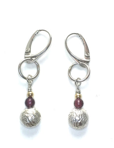 Textured reticulated silver metal with smooth reddish purple  round garnets.   All hang from smooth silky jump rings and secured in the ears by secure lever back hanger.