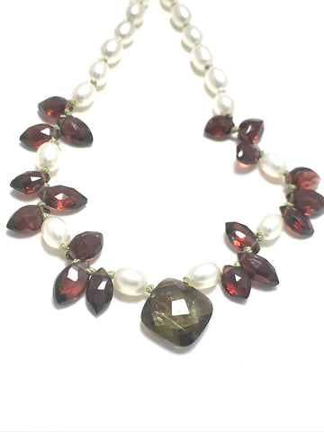 A pearl knotted necklace of white potato shaped pearls with marquise shaped red garnets and a focal point of one andalusite.   The andalusite is shaped as a rounded rectangle.   It is green with flashes of orange and lilac.