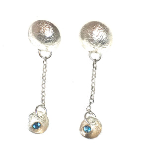 Earrings made from highly textured reticulated silver.  These earrings have posts attached to half domed moon shaped disks.   From the disks hang chain and then smaller disks in which are nestled a London blue topaz set in a gold tube set.