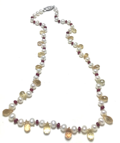 A pearl knotted piece with white pearls, yellow topaz and red rubies.