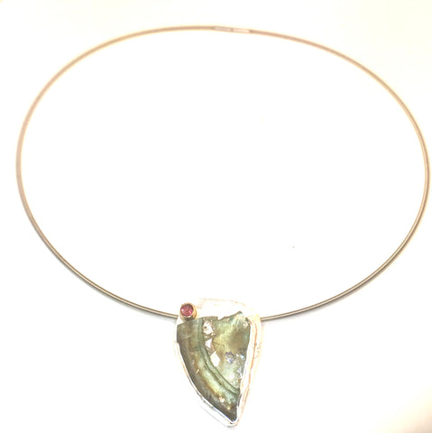 "A free form pendant of sterling silver that is set with a 2000 year-old Roman glass shard from Israel.    The shard shows the beautiful rainbow of iridescence colors from minerals in the ground. Tactile texture. A purple/reddish garnet is set at the top to accent the green color of the Roman glass.   Price includes an 18""L sterling silver cable with safety clasp."