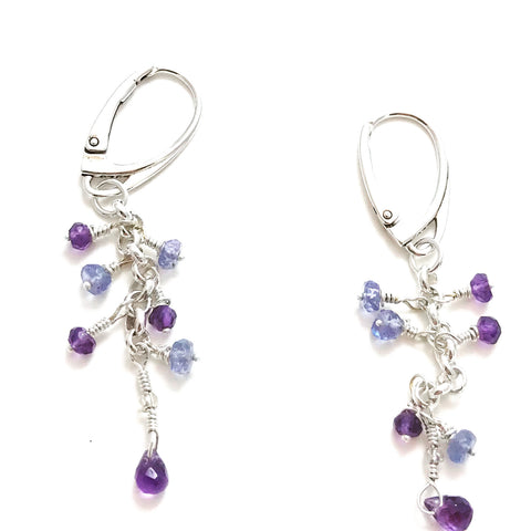 Delicate earrings that have drops of purple and light purple stones hanging.
