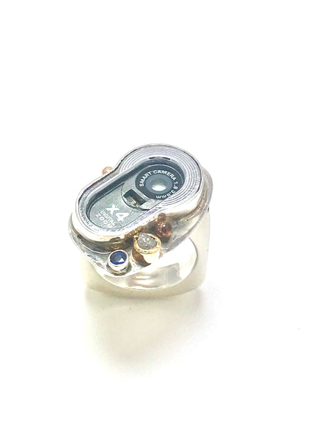 A ring made out of a cell phone camera ring.  The camera is accented with a blue sapphire and a diamond and one small gold ball.