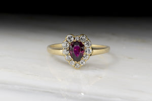 .75 Carat Pear Cut Ruby in c. 1900 Victorian 14K Rose Gold Heart Shaped Engagement Ring with Old Mine Cut Diamond Halo