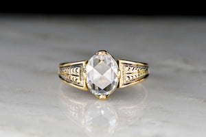 Mid-Late 1800s Gold Ring with Carved Shoulders and a Colorless Oval Rose Cut Diamond Center