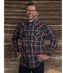 Image of MWG long-sleeve plaid shirt in wine, black, and white pattern. MWG plaid shirt has a dress-shirt style collar and two front pockets with snap button closures. Buttons are pearl snaps. Model is wearing MWG plaid shirt with MWG stretch denim jeans.