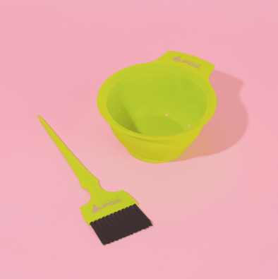 Arctic Fox Hair Color's lime green dye bowl and dye brush laid out on a pink backdrop