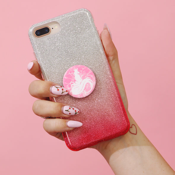 Hand holding up a pink sparkly phone case with a pink AF Pop Socket on it