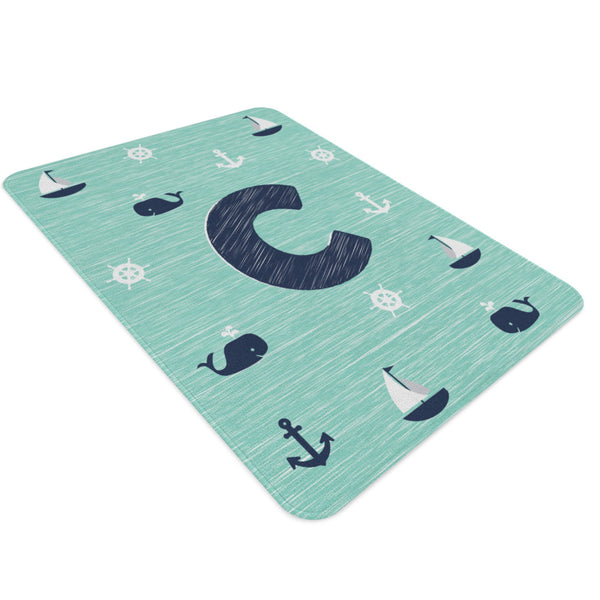 A rectangular nautical nursery rug with a monogram in the centre. It is mint and navy colored and has sailboats, whales, ship wheels and anchors on it.