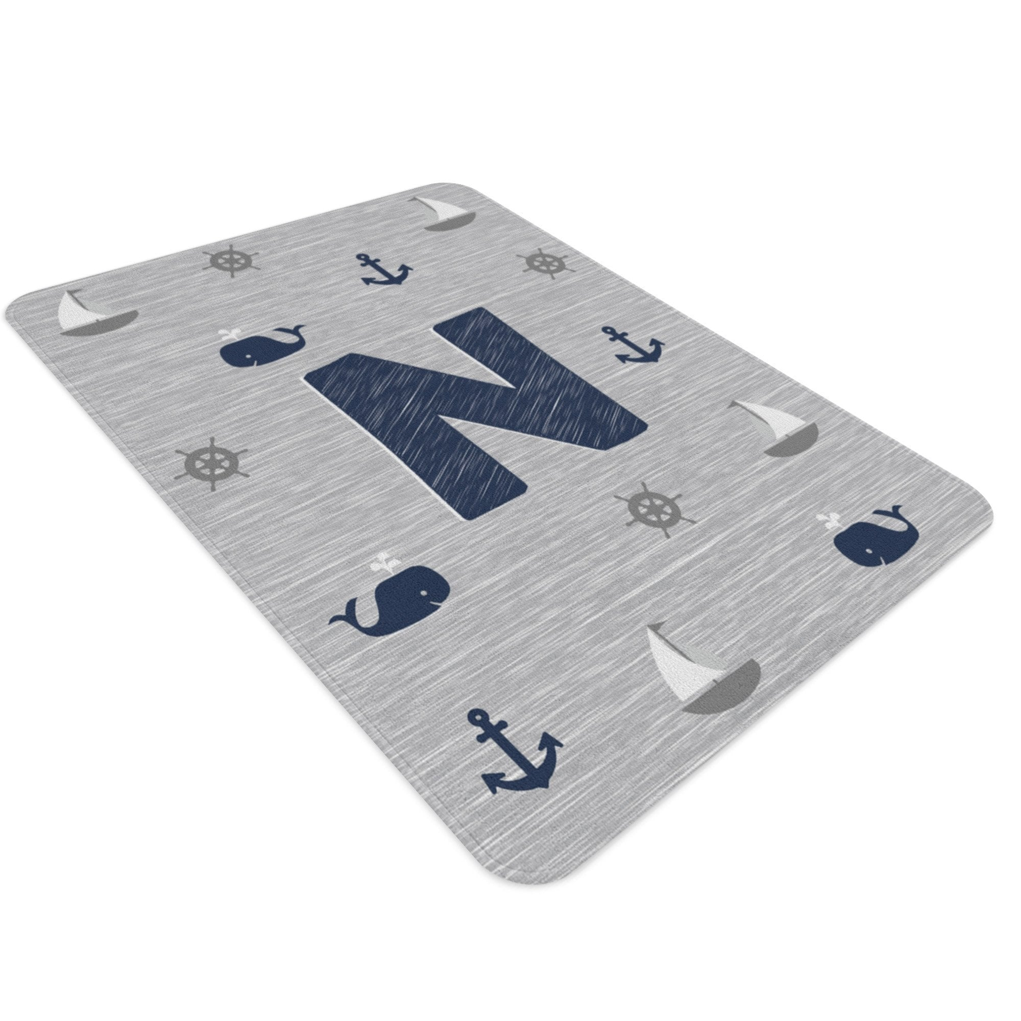 A rectangular nautical nursery rug with a monogram in the centre. It is gray and navy and has sailboats, whales, ship wheels and anchors on it.