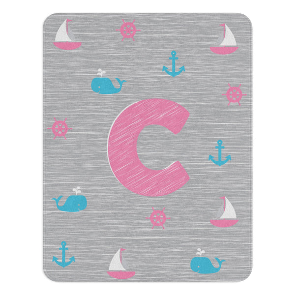 A rectangular nautical nursery rug with a monogram in the centre. It is gray and pink colored and has sailboats, whales, ship wheels and anchors on it.