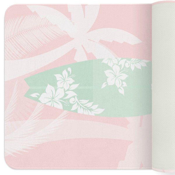 A pink nursery rug with with a mint green surfboard with silhouettes of hibiscus on it.  The rug also has silhouettes of palm trees around it. This rug is perfect for your beach themed nursery or for your kids playroom.