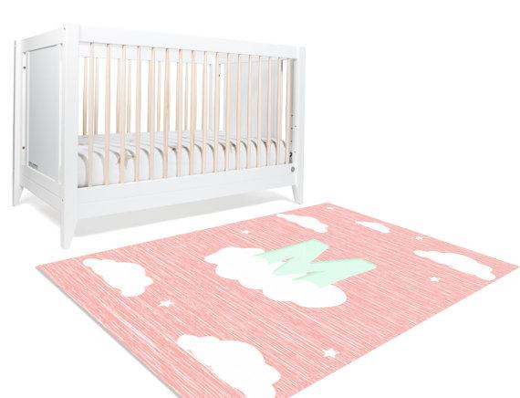 A custom cloud rug for your girl with her initial in mint perched on a cloud. This pink rug along with a sprinkle of stars is a safe choice for your baby girl's nursery or her playroom.