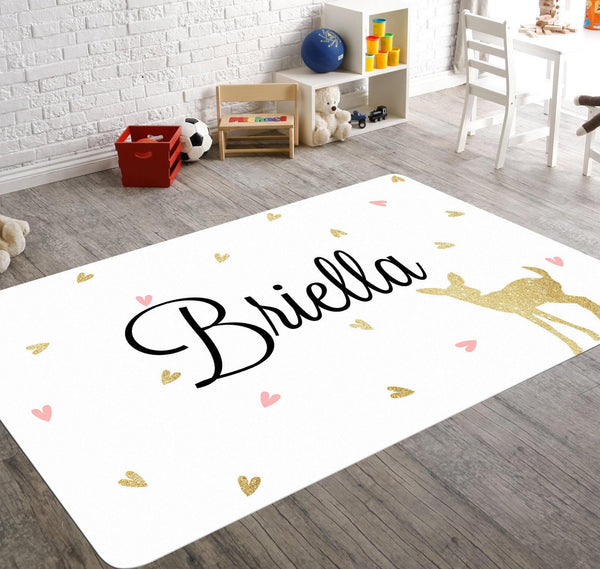 A white monogram rug with the silhouette of a fawn surrounded by heart shaped pink and golden leaves. Perfect for a woodland themed nursery and or for your child's playroom.