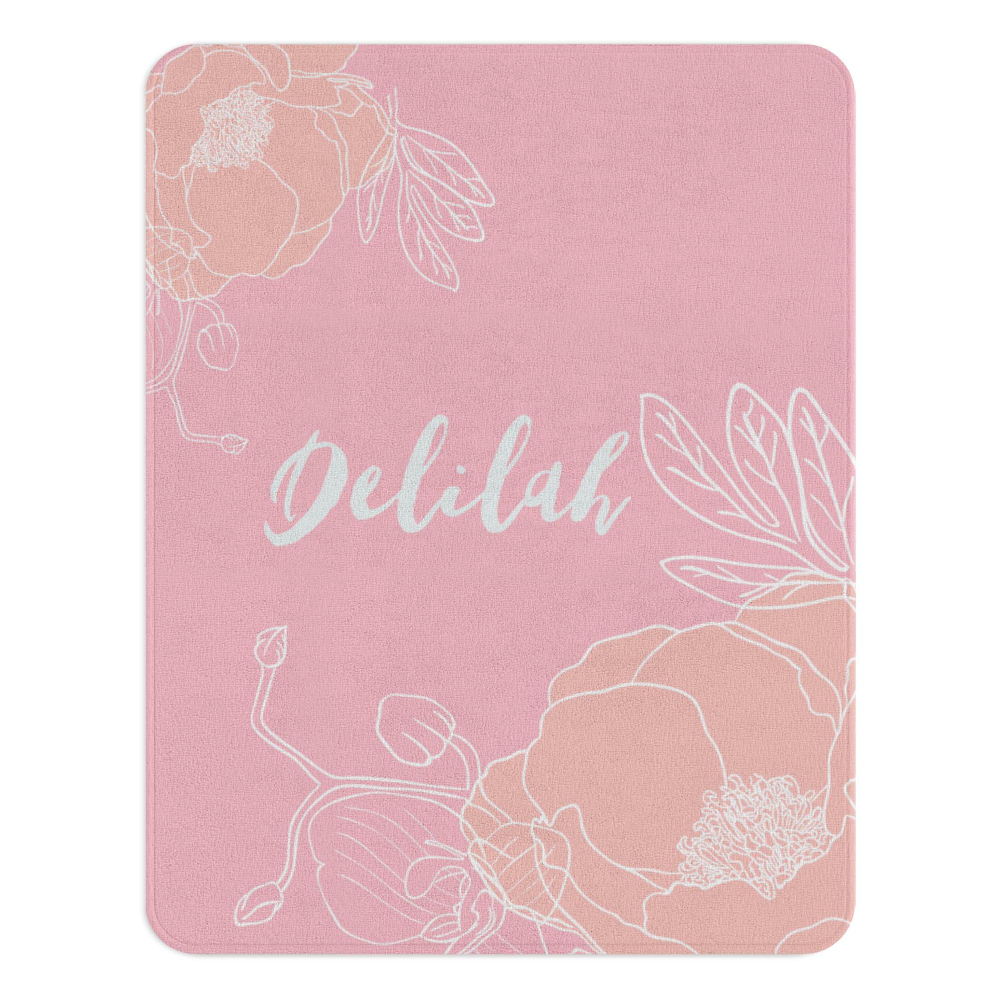 A pink floral rug with a blush flower illustration on diagonally opposite corners. The nursery rug also has a customized monogram in the center.