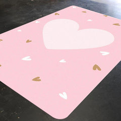 A pink nursery rug for your little girl with a big pale pink heart in the center. The rug also has small pale pink and gold hearts sprinkled all over the rug.