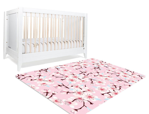 A pink floral nursery rug with sakura blooms covering the entire rug. A versatile rug for your little girl's floral themed nursery.