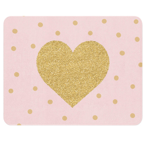 A pretty pink nursery rug with a big golden heart in the center. The golden heart is surrounded by a sprinkle of golden dots around it.