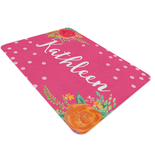 A pink floral nursery rug with white polka dots strewn around and a bunch of flowers on two diagonally opposite corners of the rug. It is customized to your child's name. Perfect for a floral themed nursery.